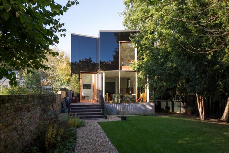 Черный дом из стекла среди деревьев